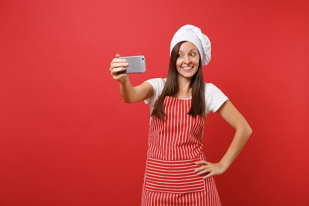 주부 여성 셰프는 줄무늬 앞치마, 흰색 티셔츠, 빨간 벽 배경에 격리된 토크 셰프 모자를 쓰고 제빵사를 요리합니다. 휴대 전화에서 셀카 촬영을 하 고 웃 고 재미 있는 여자. 복사 공간 개념을 비웃습니다.