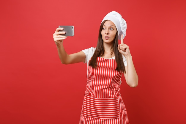주부 여성 셰프는 줄무늬 앞치마, 흰색 티셔츠, 빨간 벽 배경에 격리된 토크 셰프 모자를 쓰고 제빵사를 요리합니다. 휴대 전화에서 셀카 촬영을 하 고 웃 고 재미 있는 여자. 복사 공간 개념을 비웃습니다. 프리미엄 사진