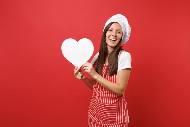 Повар шеф-повара домохозяйки или пекарь в полосатом фартуке, белой футболке, шляпе шеф-повара toque изолированной на красной предпосылке стены. усмехаясь место работы сердца владением домработницы пустое сердце. копируйте концепцию пространства копии.