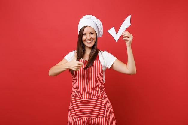 縞模様のエプロン、白いtシャツ、赤い壁の背景に分離されたトーク帽のシェフの帽子の主婦女性シェフ料理人またはパン屋。サインをするために小切手を保持している笑顔の家政婦の女性。コピースペースの概念をモックアップします。