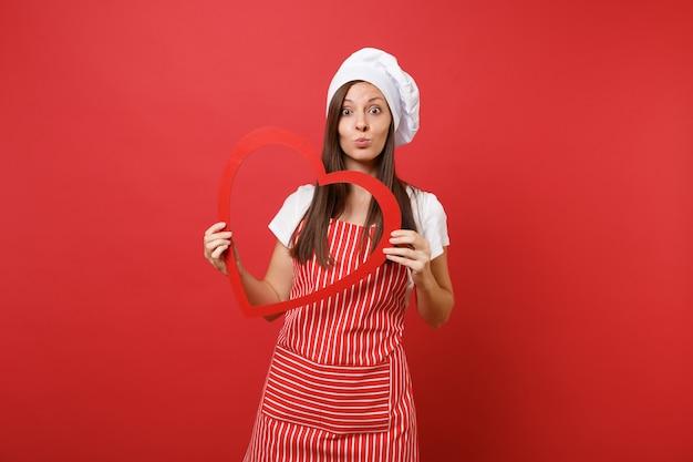 Повар шеф-повара домохозяйки или пекарь в полосатом фартуке, белой футболке, шляпе шеф-повара toque изолированной на красной предпосылке стены. улыбается женщина экономка, держащая деревянное красное сердце. копируйте концепцию пространства копии.