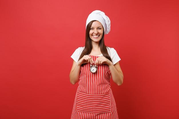 Повар шеф-повара домохозяйки или пекарь в полосатом фартуке, белой футболке, шляпе шеф-повара toque изолированной на красной предпосылке стены. улыбающаяся женщина держит в руке ретро-будильник, торопитесь. копируйте концепцию пространства копии.