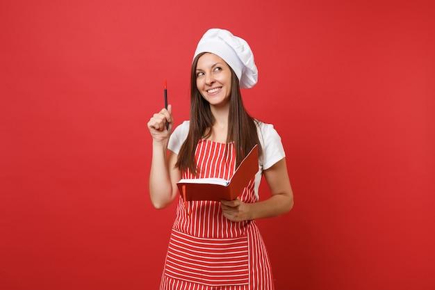 Повар или пекарь домохозяйки женский шеф-повар в полосатом фартуке белой футболке toque повара шляпе изолированной на красном фоне стены. усмехаясь книга и ручка рецепта блокнота владением женщины. копируйте концепцию пространства копии.