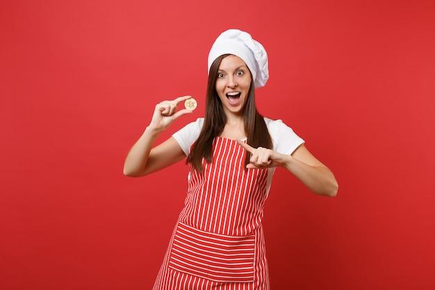 붉은 벽 배경에 격리된 줄무늬 앞치마 흰색 티셔츠 토크 셰프 모자를 쓴 주부 여성 요리사 또는 제빵사. 비트코인, 비트코인 미래 화폐를 들고 웃는 여자. 복사 공간 개념을 비웃습니다.