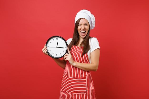 Повар шеф-повара домохозяйки или пекарь в полосатом фартуке, белой футболке, шляпе шеф-повара toque изолированной на красной предпосылке стены. улыбающаяся женщина, держащая в руке круглые часы, торопитесь. копируйте концепцию пространства копии.