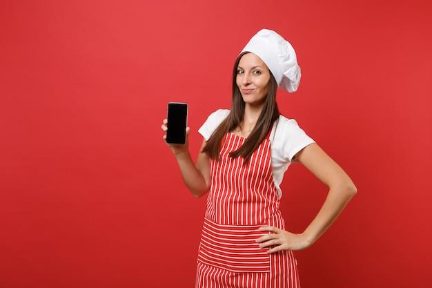 붉은 벽 배경에 격리된 줄무늬 앞치마 흰색 티셔츠 토크 셰프 모자를 쓴 주부 여성 요리사 또는 제빵사. 여자는 판촉 콘텐츠를 위해 휴대폰 빈 화면을 들고 복사 공간 개념을 조롱합니다.