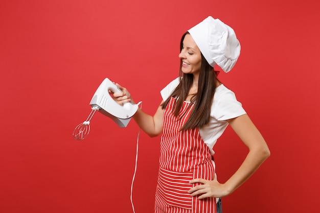 Повар или пекарь домохозяйки женский шеф-повар в полосатом фартуке белой футболке toque повара шляпе изолированной на красном фоне стены. смеситель кухни владением женщины, готовьте рождественское имбирное печенье. копируйте концепцию пространства копии.