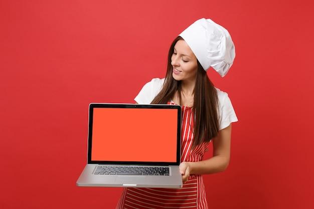 붉은 벽 배경에 격리된 줄무늬 앞치마 흰색 티셔츠 토크 셰프 모자를 쓴 주부 여성 요리사 또는 제빵사. 여성은 판촉 콘텐츠를 위해 노트북 pc 빈 화면을 들고 복사 공간 개념을 조롱합니다.