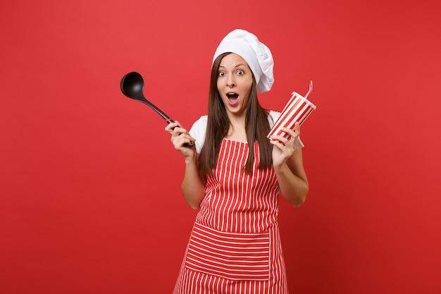縞模様のエプロン、白いtシャツ、赤い壁の背景に分離されたトーク帽のシェフの帽子の主婦女性シェフ料理人またはパン屋。女性はスープ黒取鍋ディッパー、プラスチックカップコーラを保持します。コピースペースの概念をモックアップします。