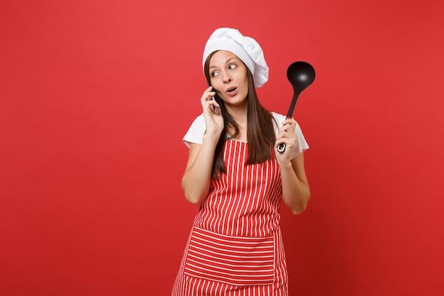 赤い壁の背景に分離された縞模様のエプロン白いtシャツトークシェフの帽子の主婦女性シェフ料理人またはパン屋。女性は携帯電話でスープ黒取鍋ディッパートークを保持します。コピースペースの概念をモックアップします。