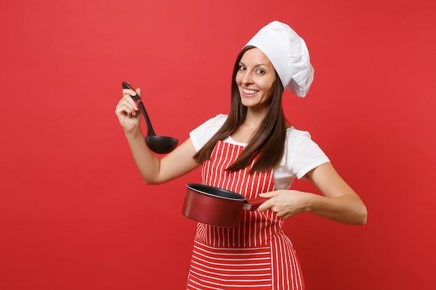 赤い壁の背景に分離された縞模様のエプロン白いtシャツトークシェフの帽子の主婦女性シェフ料理人またはパン屋。女性は空のシチューパン黒スープ取鍋ディッパーを試飲します。コピースペースの概念をモックアップ