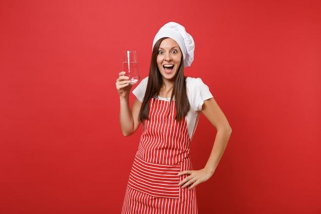 붉은 벽 배경에 격리된 줄무늬 앞치마 흰색 티셔츠 토크 셰프 모자를 쓴 주부 여성 요리사 또는 제빵사. 유리에서 맑고 신선한 순수한 물을 마시는 들고 여자. 복사 공간 개념을 모의