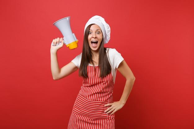 縞模様のエプロン、白いtシャツ、赤い壁の背景に分離されたトーク帽のシェフの帽子の主婦女性シェフ料理人またはパン屋。女性がメガホンで悲鳴を上げ、割引セールを発表。コピースペースの概念をモックアップします。