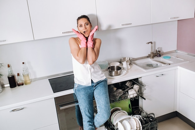家を掃除した後のピンクの手袋の主婦の女の子は感情的で白いキッチンで疲れています