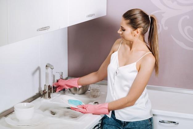 분홍색 장갑에 주부 소녀 세제로 싱크대에 손으로 요리를 씻어. 소녀는 집을 청소하고 집에서 장갑을 끼고 설거지를합니다.