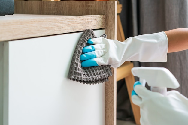 Housewife hands in rubber protective glove with micro fiber cloth and detergent cleaning a cupboard surface in living room