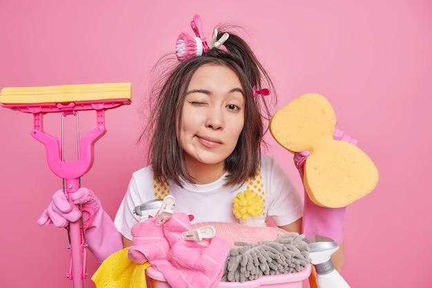 主婦は散らかった髪のウインクを持っています目はあなたに掃除サービスを提供しますきれいなスポンジとモップは家事で忙しいプロの掃除人です