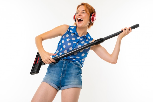 Housewife in headphones cleans the room with a vacuum cleaner on a white wall