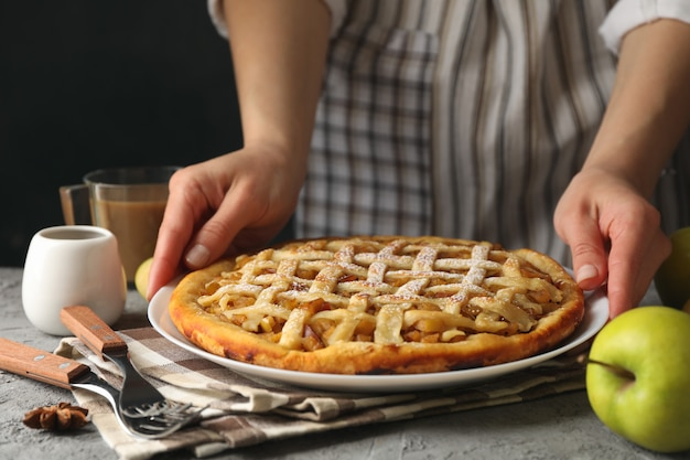 Housewife hold tasty apple pie on gray table