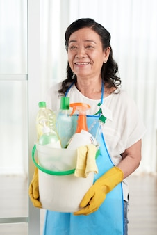 Housewife holding bucket full of detergents