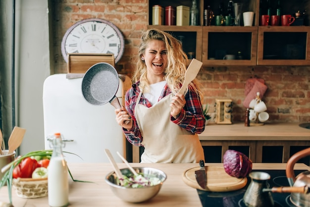 Домохозяйка держит сковороду и деревянную лопатку