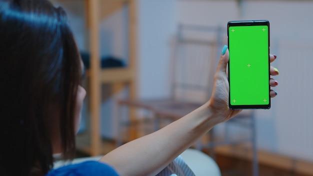 크로마 스크린이 있는 스마트폰을 들고 흉내를 내는 주부. 아늑한 소파에 앉아 기술 인터넷을 사용하여 녹색 화면 템플릿 크로마 키 격리 휴대폰 디스플레이에서 읽기
