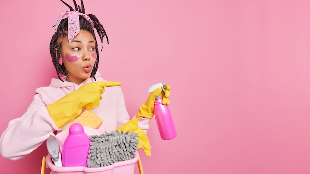 Housewife holds spray detergents ready for cleaning service indicates aside on copy space gives ideas or tips wears rubber gloves casual clothes isolated on pink