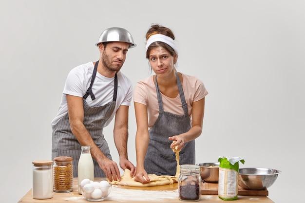 Casalinga e marito impastano la pasta con le mani, cuociono insieme la pizza fatta in casa, preparano una cena festiva per la famiglia o gli ospiti, indossano grembiuli, essendo un po 'stanchi, posano in cucina contro il muro bianco