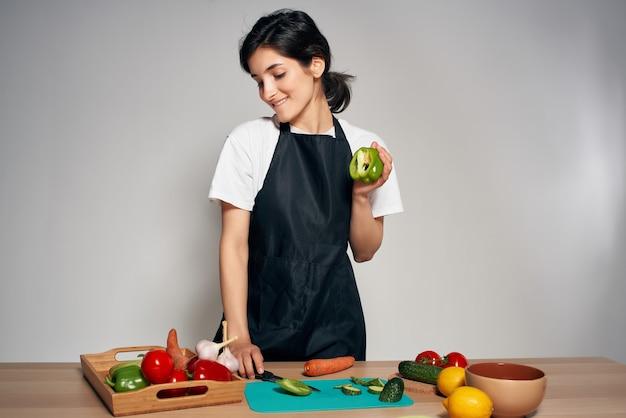 キッチンの黒いエプロンの主婦新鮮な野菜の健康食品