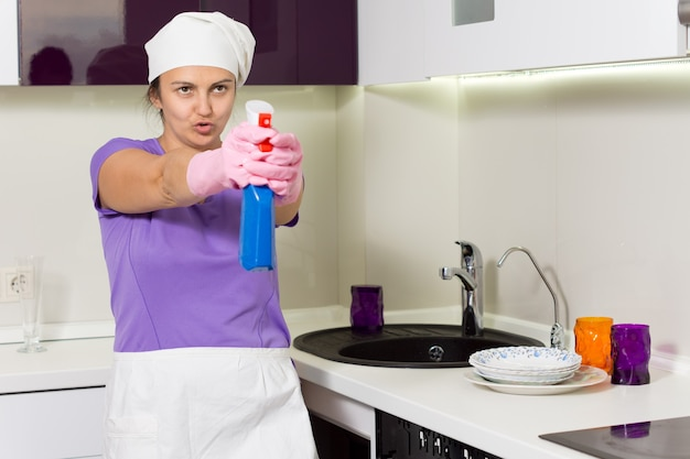 Домохозяйка в фартуке и белой кепке весело целится из распылителя моющего средства
