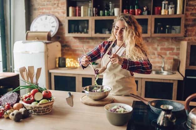 キッチンで新鮮なサラダを調理するエプロンの主婦