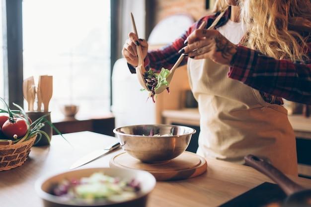 Домохозяйка в фартуке готовит свежий салат на кухне