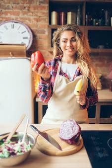Домохозяйка в фартуке держит в руках свежий перец