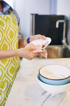 Домохозяйка в фартуке протирает вымытую и ополоснутую посуду