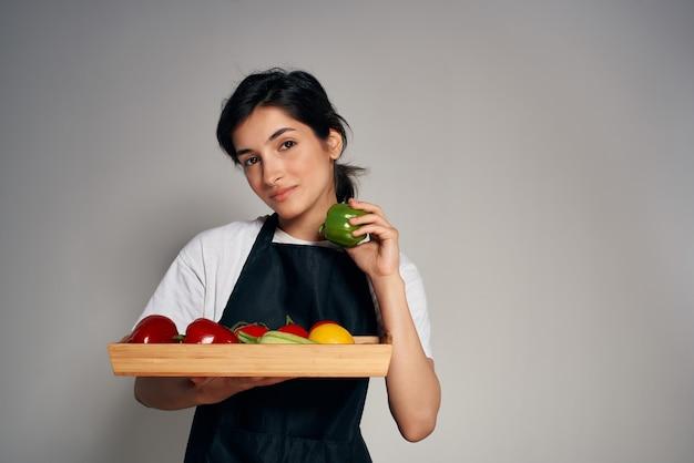 黒エプロン野菜生鮮食品明るい背景の主婦
