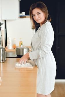 朝の生活の中で朝食を調理するキッチンに立っている家庭用綿バスローブの主婦