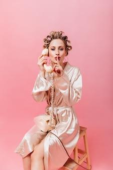 분홍색 가운을 입은 주부 전화로 험담하고 그녀의 손가락을 입에 넣습니다.