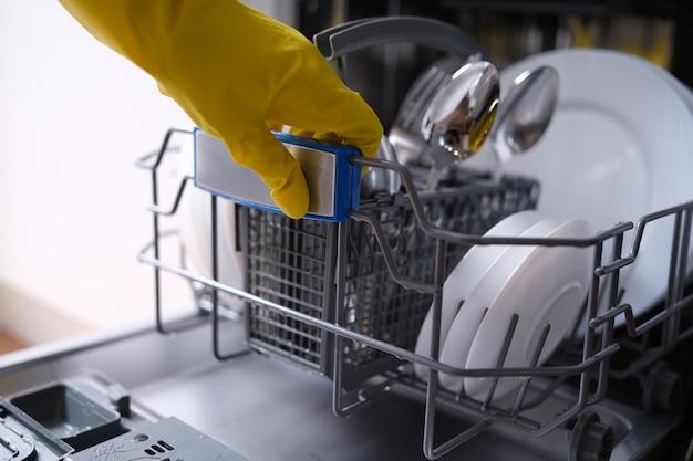 고무 장갑을 끼고 식기 세척기 근접 촬영에서 깨끗한 접시를 얻는 주부