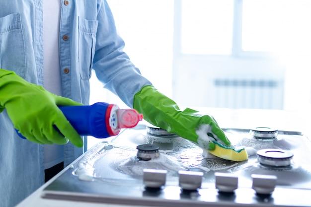 Домохозяйка в резиновых перчатках моет и полирует газовую плиту с чистящими средствами