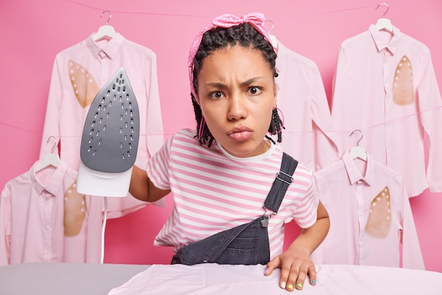 Домохозяйка гладит семейную одежду.