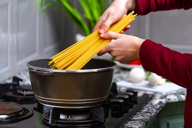 Housewife is cooking spaghetti in a saucepan for a lunch at home