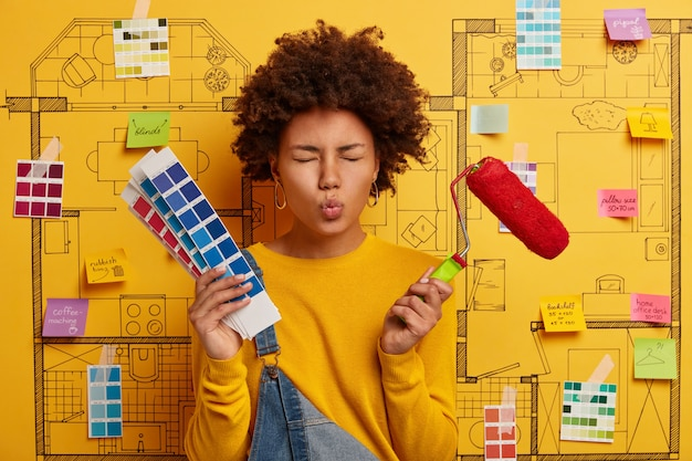 Housewife keeps lips rounded, busy with house renovation, holds paint brush and color palette, makes repair in apartmet according to design project. house painter poses over sketch on yellow wall