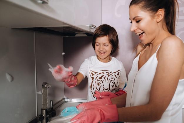ピンクの手袋をした主婦のお母さんは、洗剤で流しに手で息子と一緒に皿を洗います