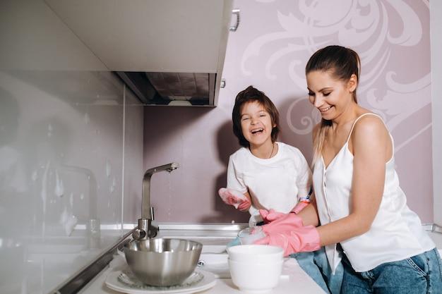 Домохозяйка мама в розовых перчатках моет посуду вместе с сыном вручную в раковине с моющим средством