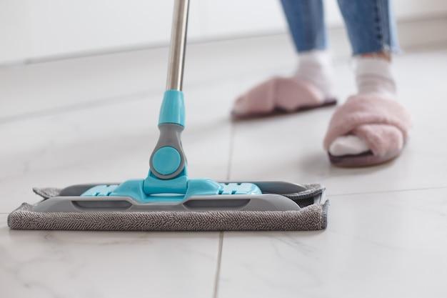 Housewife mopping floor made of porcelain tiles in the kitchen.