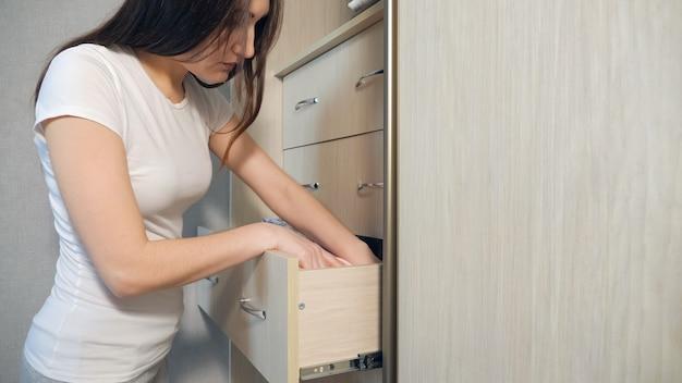 Домохозяйка организовывает одежду в шкафу, крупным планом.