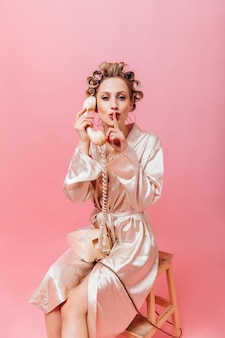 Housewife in pink robe gossiping on phone and puts her finger to her mouth
