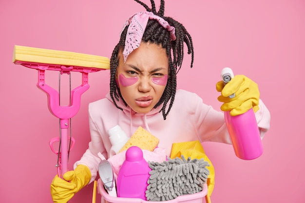 Housewife poses with housecleaner tools cares about purity smirks face looks scrupulously at something dirty holds mop cleaning detergent isolated on pink