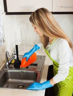 洗剤をシンクに注ぐ主婦 無料写真