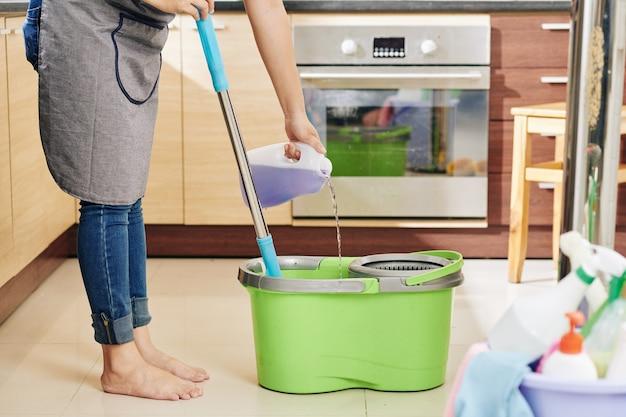 床の洗浄液を注ぐ主婦